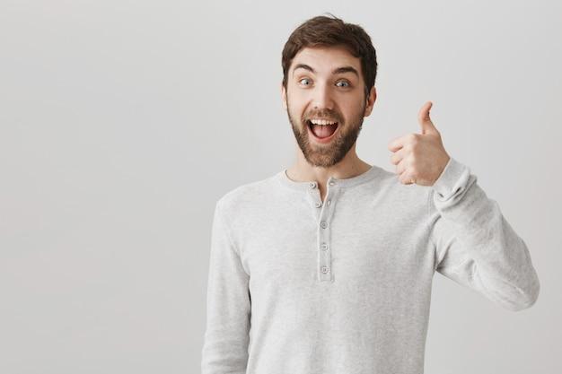 Zadowolony, uśmiechnięty, brodaty klient mężczyzna pokazuje kciuki do góry z aprobatą