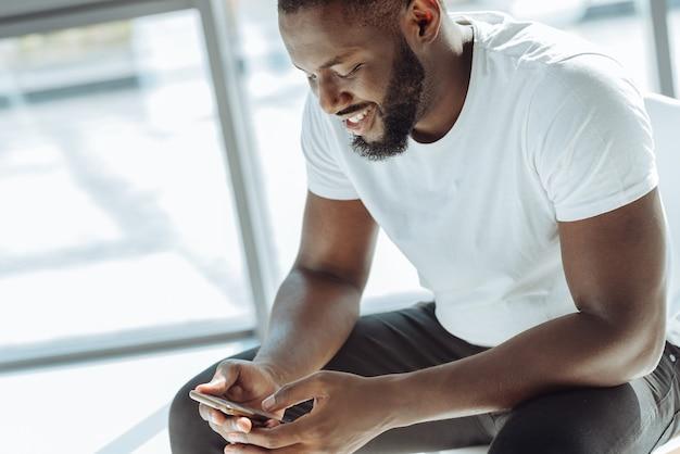 Zadowolony użytkownik. pozytywny młody afro-amerykański mężczyzna siedzi w pomieszczeniu i uśmiecha się whule za pomocą swojego smartfona