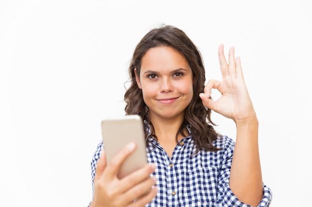 Zadowolony użytkownik telefonu polecający nową aplikację mobilną
