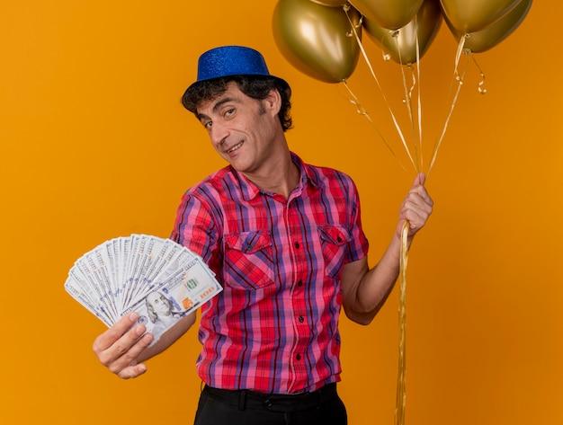 Zadowolony w średnim wieku kaukaski mężczyzna w kapeluszu z balonów, trzymając balony i wyciągając pieniądze w kierunku kamery, patrząc na kamerę na białym tle na pomarańczowym tle