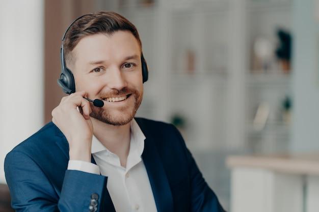 Zadowolony wesoły brodaty mężczyzna pracownik biurowy w garniturze doradztwo klientów siedząc i używając zestawu słuchawkowego w domu lub biurze, selektywne skupienie się na uśmiechniętym człowieku. koncepcja pracy i zawodu