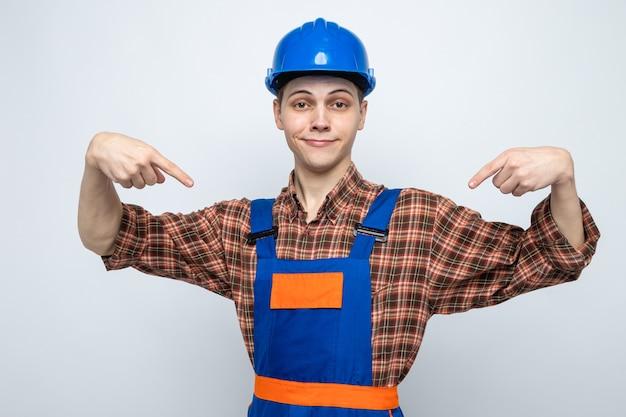 Zadowolony wskazuje na siebie młodego budowniczego mężczyzny noszącego mundur