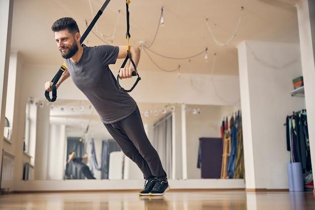 Zadowolony wysportowany mężczyzna z tułowiem opuszczonym w kierunku podłogi i zgiętymi łokciami podczas wyciskania klatki piersiowej trx