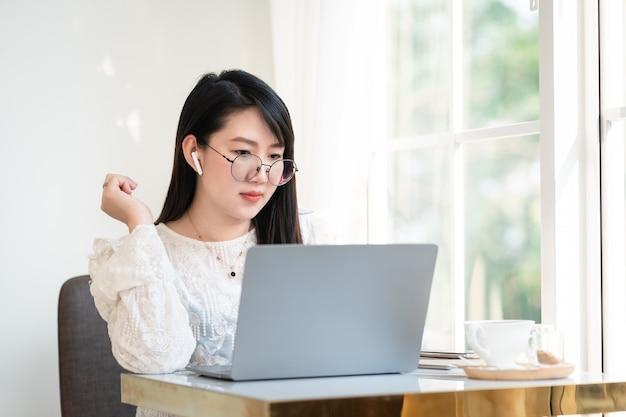 Zadowolony z azjatyckich niezależnych ludzi bizneswoman nosi bezprzewodowe słuchawki dorywczo pracując z laptopem z kubkiem na filiżankę kawy, notebookiem i smartfonem w kawiarni, komunikacja business lifestyle