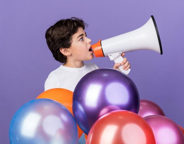 Zadowolony z boku mały chłopiec stojący za balonami mówi przez głośnik