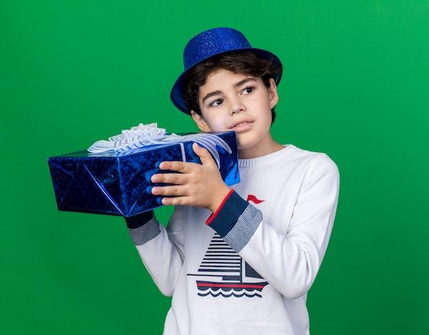 Zadowolony z boku mały chłopiec w niebieskim kapeluszu na imprezę, trzymający pudełko na prezent