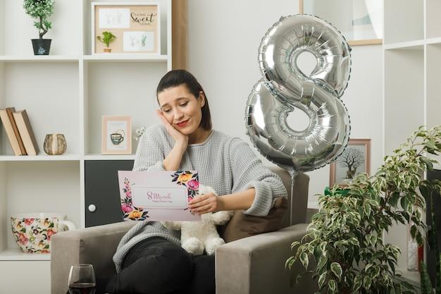 Zadowolony z kładzenia dłoni na policzku piękna dziewczyna w szczęśliwy dzień kobiet trzymająca i czytająca kartkę z życzeniami siedzącą na fotelu w salonie