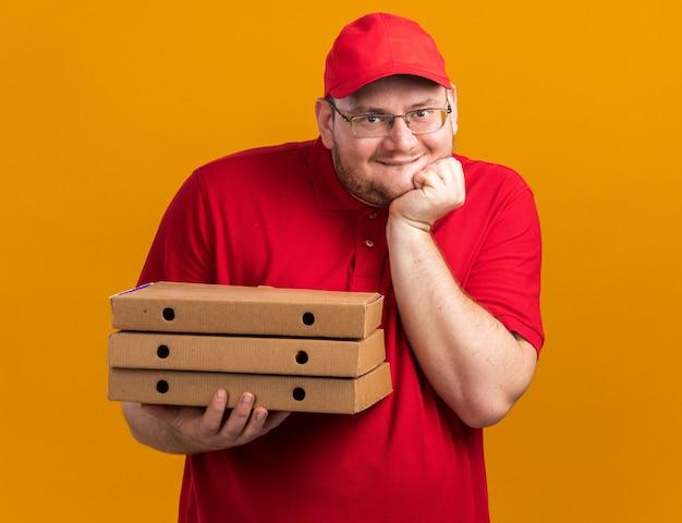 Zadowolony z nadwagą młody doręczyciel w okularach optycznych trzymający pudełka po pizzy i kładący rękę na brodzie, odizolowany na pomarańczowej ścianie z miejscem na kopię