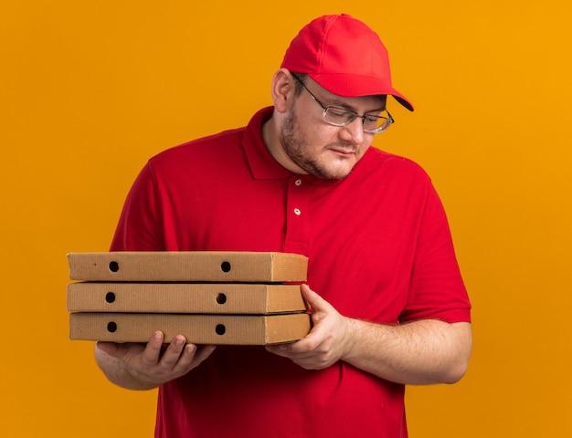 Zadowolony z nadwagą młody doręczyciel w okularach optycznych trzymający pudełka po pizzy i patrzący w dół odizolowany na pomarańczowej ścianie z miejscem na kopię