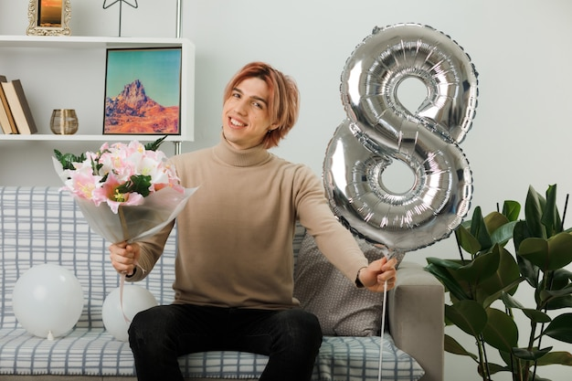 Zadowolony z przechylaną głową przystojny facet w szczęśliwy dzień kobiet trzymający balon numer osiem i bukiet siedzący na kanapie w salonie