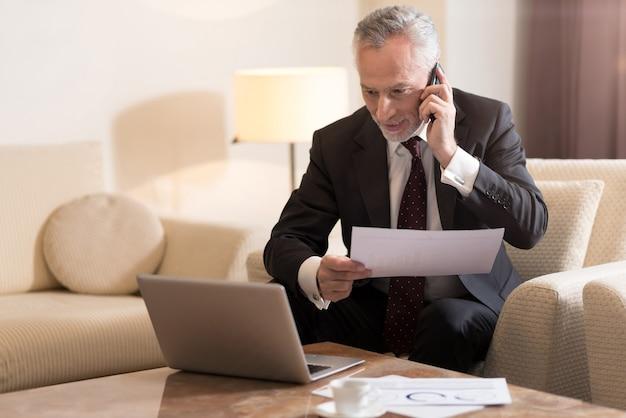 Zadowolony z rozmowy. uśmiechnięty zachwycony brodaty biznesmen rozmawia przez telefon i siedzi w hotelu przed laptopem, pracując z papierami i wyrażając podekscytowanie