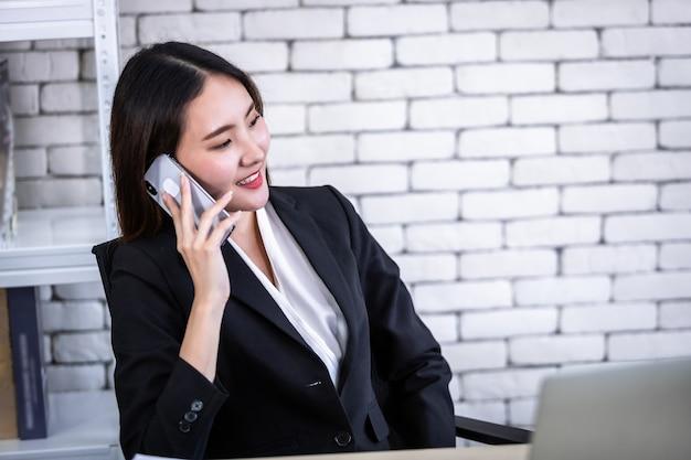 Zadowolony z udanej azjatyckiej młodej bizneswoman przytrzymaj odebrać smartfona pracującego z laptopem na białym drewnianym stole w białej ścianie w tle biurowym