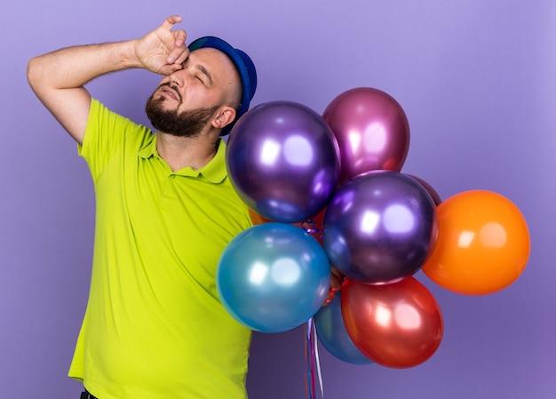 Zadowolony z zamkniętych oczu młody mężczyzna w imprezowym kapeluszu, trzymający balony, wycierając oko ręką