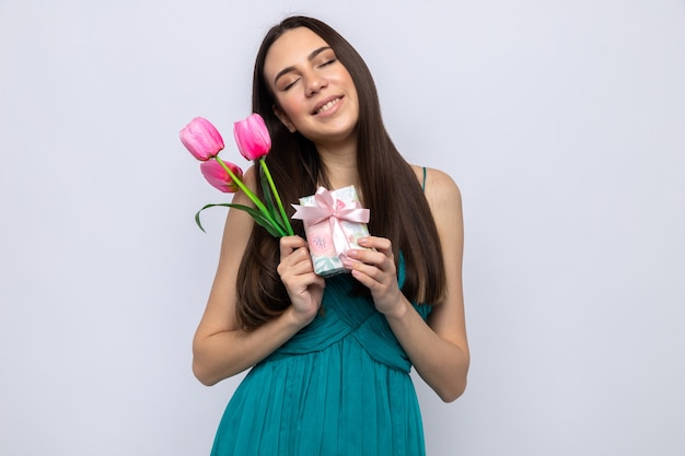 Zadowolony z zamkniętych oczu przechylających głowę piękna młoda dziewczyna w szczęśliwy dzień kobiety trzymająca prezent z kwiatami na białej ścianie