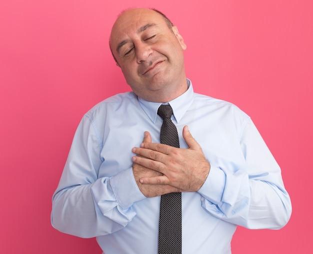 Zadowolony z zamkniętymi oczami mężczyzna w średnim wieku ubrany w białą koszulkę z krawatem kładący dłoń na sercu na różowej ścianie