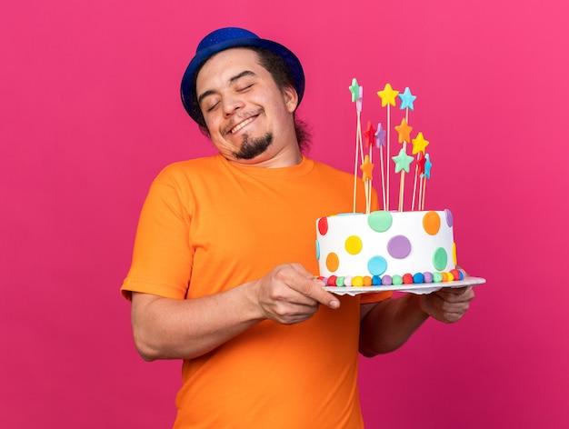 Zadowolony z zamkniętymi oczami młody mężczyzna w kapeluszu imprezowym trzymającym ciasto