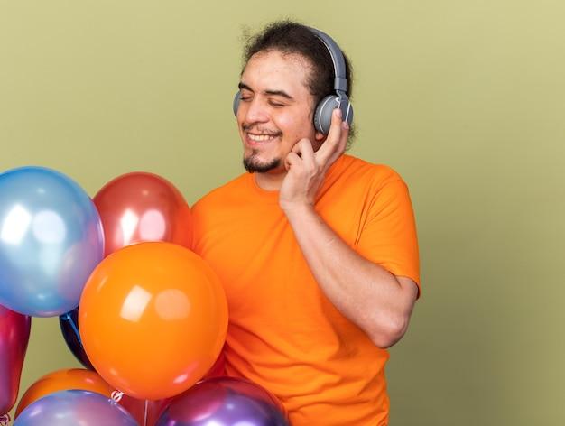 Zadowolony z zamkniętymi oczami młody mężczyzna w słuchawkach trzymający balony