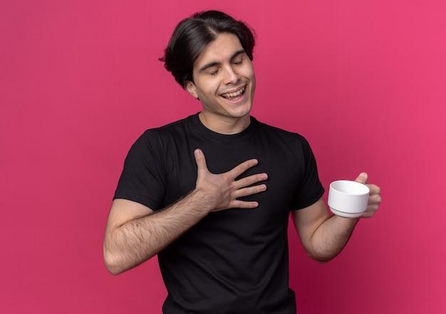 Zadowolony z zamkniętymi oczami młody przystojny facet ubrany w czarną koszulkę trzymający filiżankę kawy odizolowaną na różowej ścianie