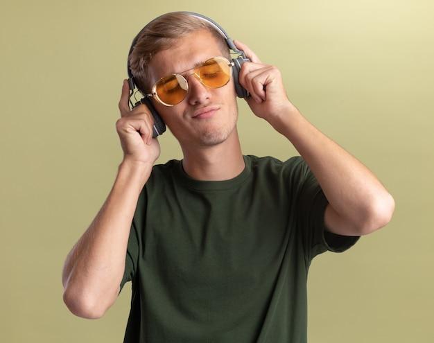 Zadowolony z zamkniętymi oczami, młody przystojny facet w zielonej koszuli z okularami i słuchawkami, odizolowany na oliwkowej ścianie