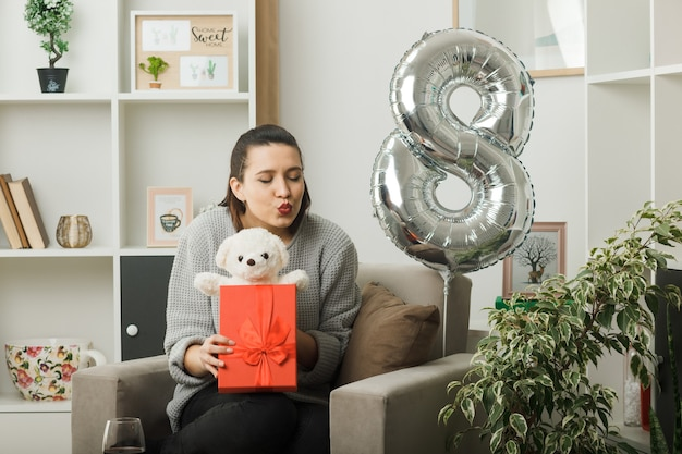 Zadowolony z zamkniętymi oczami pokazującymi gest pocałunku piękna dziewczyna na szczęśliwy dzień kobiet trzymająca prezent z misiem siedzącym na fotelu w salonie