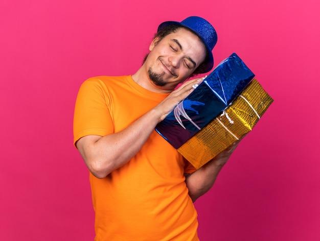 Zadowolony z zamkniętymi oczami, przechylający głowę, młody mężczyzna w kapeluszu imprezowym, trzymający pudełka na prezenty na różowej ścianie