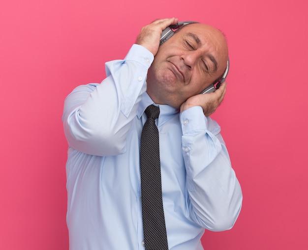 Zadowolony z zamkniętymi oczami przechylającymi głowę mężczyzną w średnim wieku w białej koszulce z krawatem i słuchawkami odizolowanymi na różowej ścianie