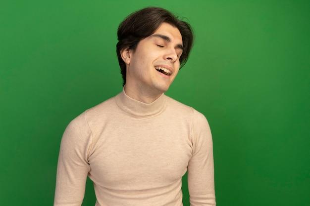 Zadowolony z zamkniętymi oczami przechylającymi głowę młody przystojny facet na białym tle na zielonej ścianie