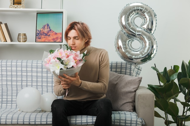 Zadowolony z zamkniętymi oczami przystojny facet w szczęśliwy dzień kobiet trzymający bukiet siedzący na kanapie w salonie