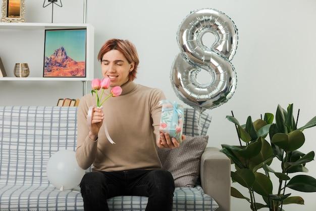 Zadowolony z zamkniętymi oczami przystojny facet w szczęśliwy dzień kobiet trzymający kwiaty z prezentem siedzącym na kanapie w salonie