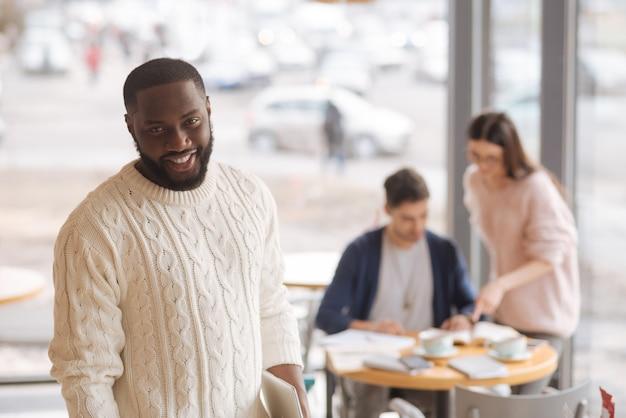 Zadowolony z życia. szczęśliwy miły mulat stojący w kawiarni na tle swoich kolegów pracujących kolegów.