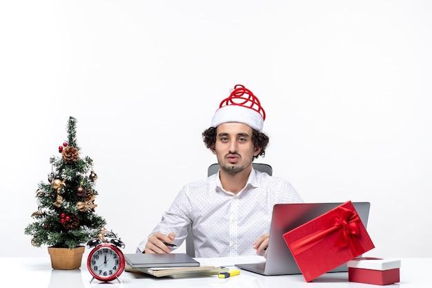 Zadowolony, zapracowany młody biznesmen z zabawnym czapką świętego mikołaja, sprawdzający pisanie notatek i świętujący boże narodzenie w biurze na białym tle