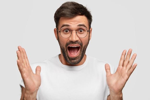 Zadowolony, zaskoczony, brodaty młody mężczyzna składa ręce i otwiera usta z radosnym wyrazem
