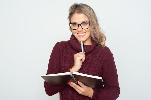 Zadowolony żeńskiego ucznia mienia notatnik i pióro