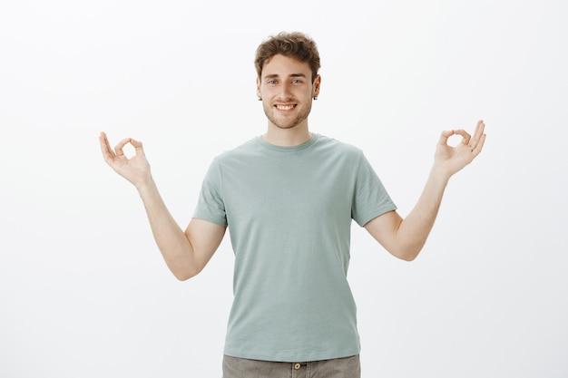 Zadowolony zrelaksowany przystojny facet w kolczykach i luźnej koszulce, uśmiechnięty szeroko
