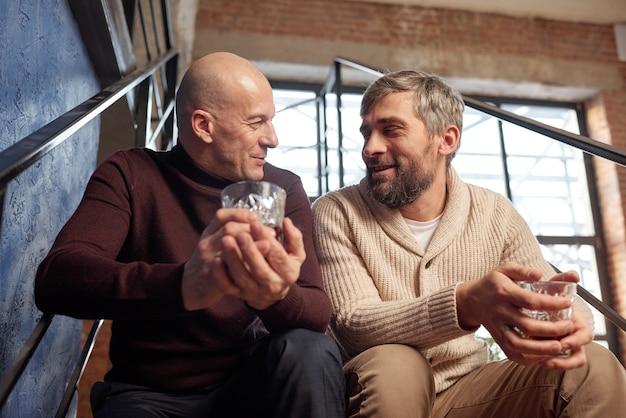 Zadowolonych mężczyzn w średnim wieku w swetrach, siedzących na schodach i pijących mocny alkohol, rozmawiając o życiu