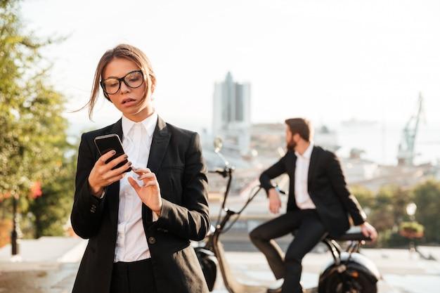Zadumana biznesowa kobieta pozuje outdoors i używa telefon