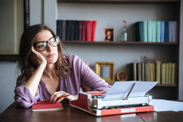 Zadumana dojrzała autorka w okularach myśli i odwraca wzrok