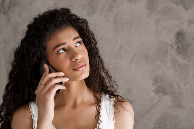 Zadumana kobieta opowiada na telefonie komórkowym