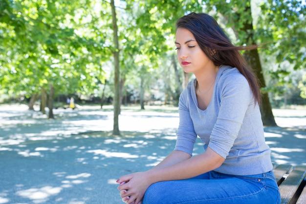 Zadumana ładna młoda dama odpoczywa w parku