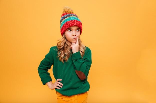 Zadumana młoda dziewczyna w swetrze i kapeluszu z ręką na biodrze, odwracając wzrok nad pomarańczą