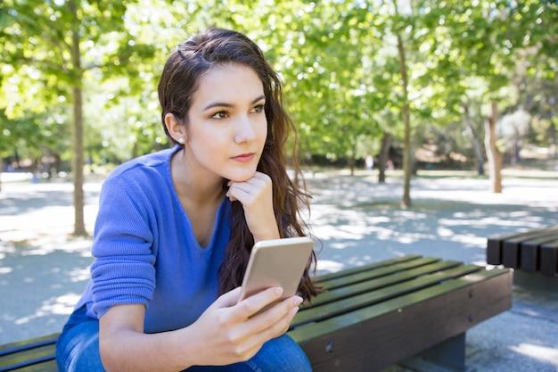 Zadumana młoda kobieta używa smartphone w parku