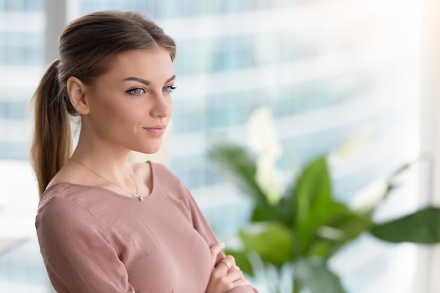 Zadumana rozważna młoda kobieta patrzeje przez okno, ręki krzyżować, indoors