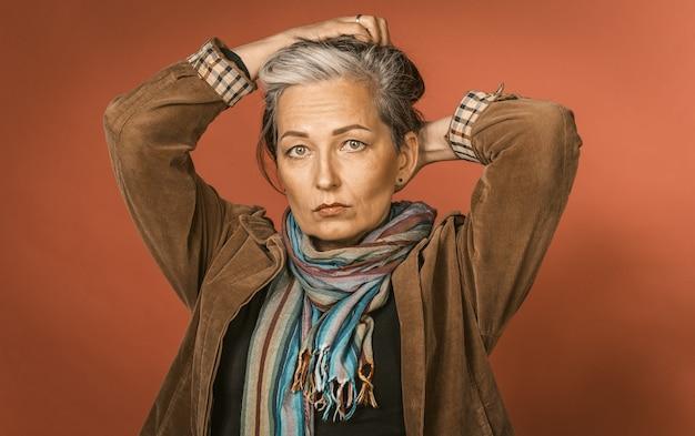 Zadumana siwowłosa kobieta robi fryzurę, zbierając włosy rękami z tyłu głowy, podczas gdy pozuje w studio na pomarańczowej ścianie. barwiony obraz