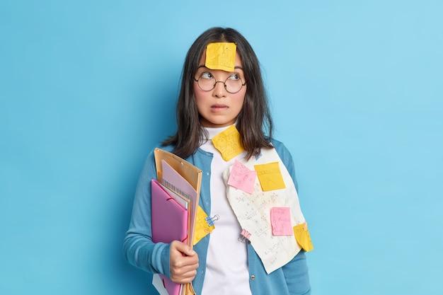 Zadumana uczennica przygotowuje się do egzaminów w szkole, przygryza usta i skupia się na nauce informacji, zanim test z matematyki założy okrągłe okulary do korekcji wzroku.