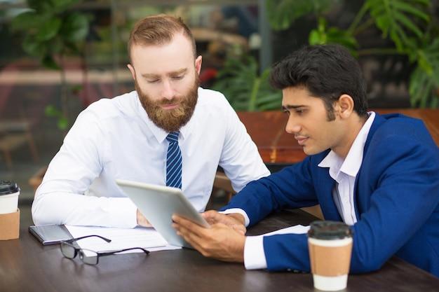 Zadumani koledzy używający nowożytnego przyrząd podczas gdy brać statystyki