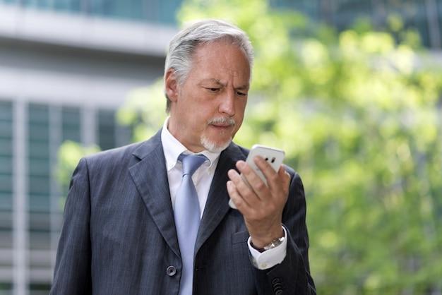 Zadumany biznesmen patrzeje jego telefon komórkowego