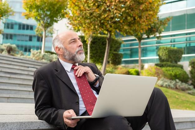 Zadumany biznesmen używa laptop na krokach