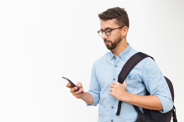 Zadumany facet z plecakiem używa smartphone