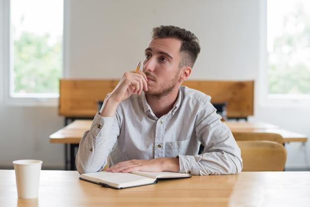 Zadumany męskiego ucznia obsiadanie przy biurkiem w sala lekcyjnej