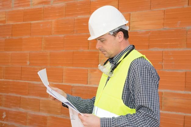 Zadumany mężczyzna rozważny młody inżynier cywilny pracuje z drukiem na budowie